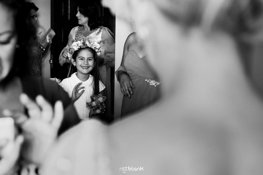 Boda en el Parador de Baiona realizado por Notblank fotografos de boda - La niña de arras sonrie a la novia