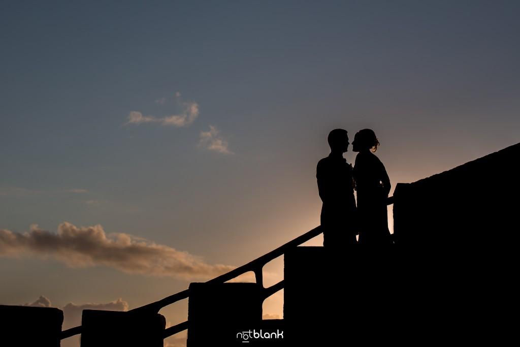 Boda en el Parador de Baiona realizado por Notblank fotografos de boda - Retrato de los novios con la puesta de sol