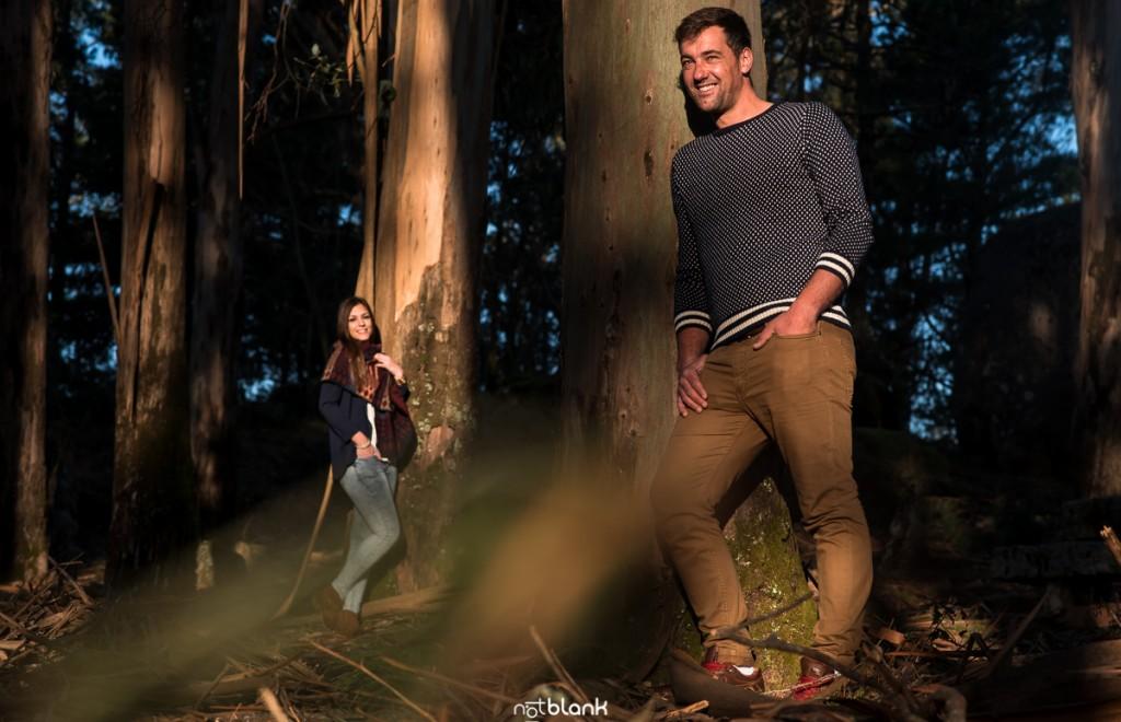 Sesión preboda en picoña. Retrato del novio apoyado sobre un árbol y la novia al fondo. Reportaje realizado por los fotógrafos de boda en Vigo Notblank.
