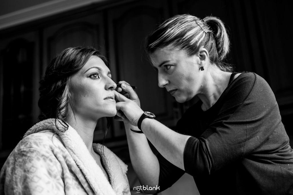 Boda en Salceda de Caselas. La maquilladora le está haciendo la aya del ojo a la novia. Reportaje realizado por Notblank fotógrafos de boda en Galicia.