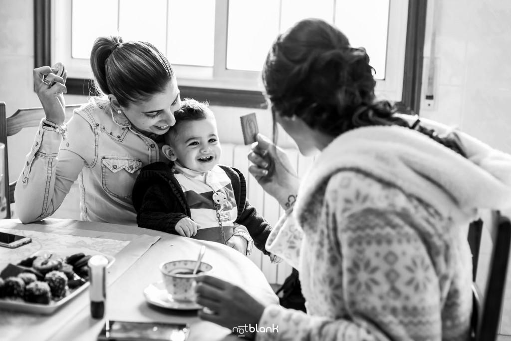 Boda en Salceda de Caselas. La novia se toma un café durante los preparativos junto a una amiga y al hijo pequeño de esta. Reportaje realizado por Notblank fotógrafos de boda en Galicia.