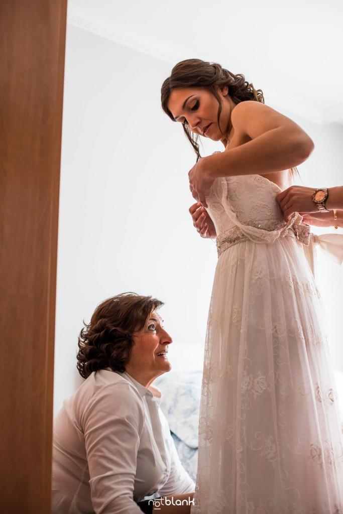 Boda en Salceda de Caselas. La madre de la novia ayuda a su hija a ponerse el vestido de boda. Reportaje realizado por Notblank fotógrafos de boda en Galicia.