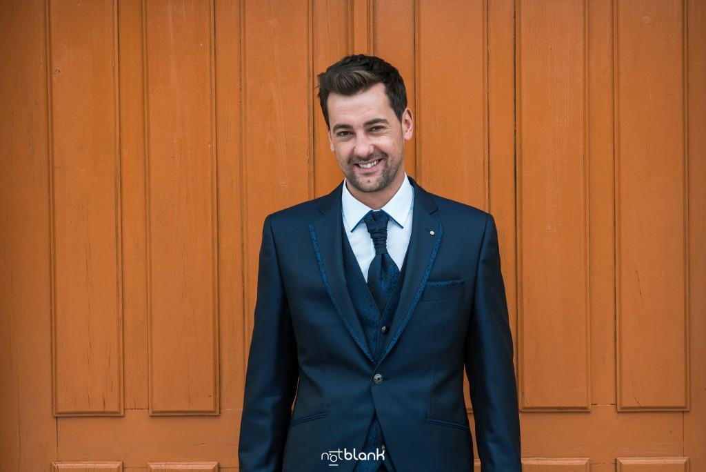 Boda en Salceda de Caselas. Retrato del novio vestido con su traje de boda azul con una puerta de madera al fondo. Reportaje realizado por Notblank fotógrafos de boda en Galicia.