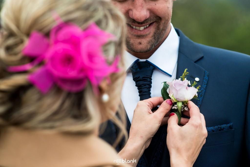 Boda en Salceda de Caselas. Una amiga del novio le coloca el botonier al novio. Reportaje realizado por Notblank fotógrafos de boda en Galicia.