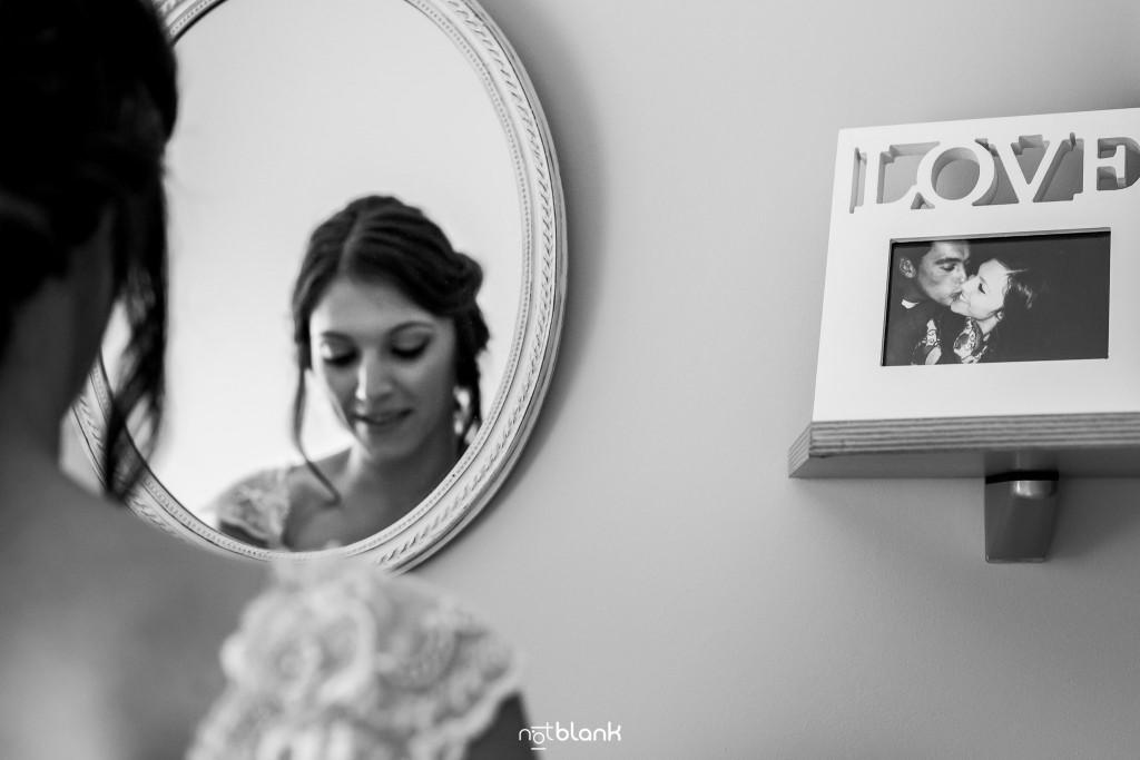Boda en Salceda de Caselas. La novia se prepara delante de un espejo en su habitación. A su derecha tiene un marco de fotos con una foto suya y su futuro marido. El marco de fotos pone LOVE (AMOR) en grande. Reportaje realizado por Notblank fotógrafos de boda en Galicia.