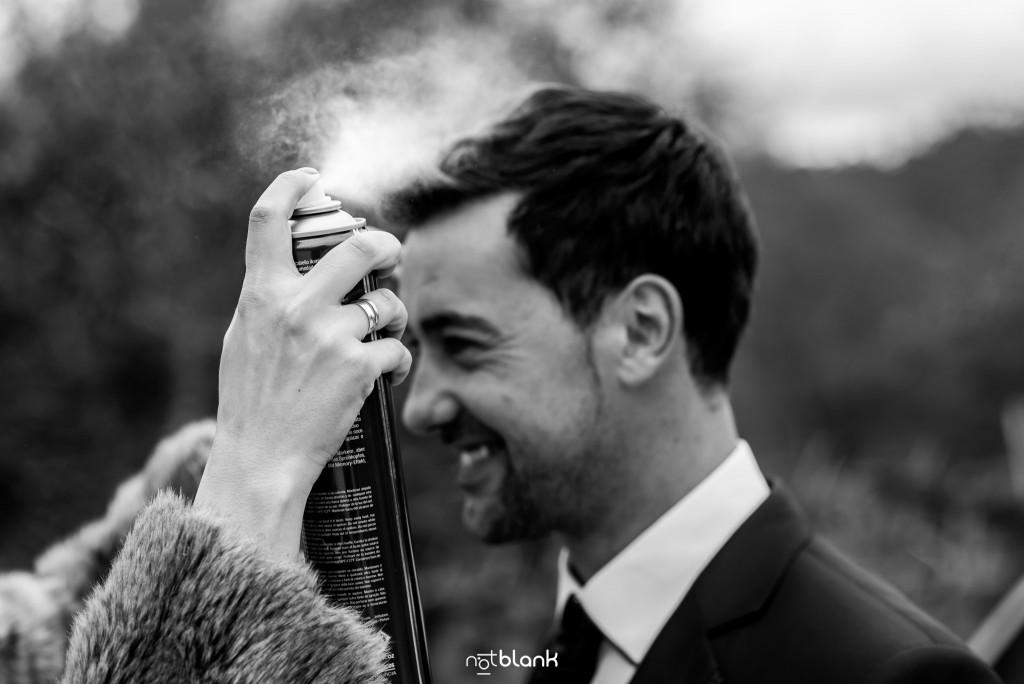 Boda en Salceda de Caselas. Una amiga le echa laca al novio justo antes de salir para la ceremonia de boda. Reportaje realizado por Notblank fotógrafos de boda en Galicia.