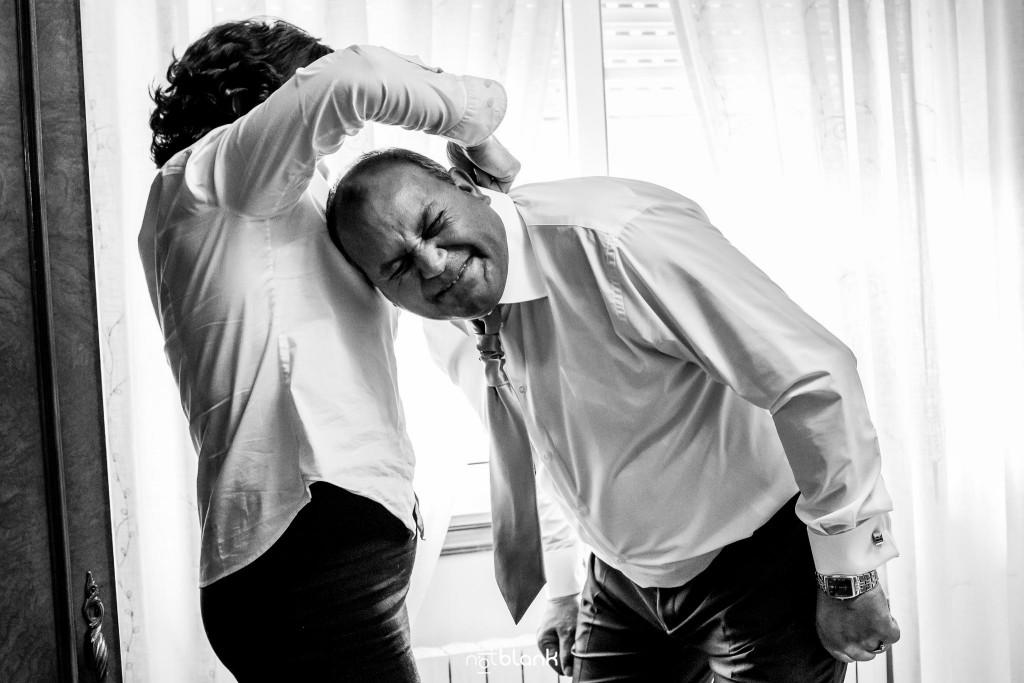 Boda en Salceda de Caselas. Los padres de la novia se preparan para la ceremonia. La madre de la novia le coloca la corbata a su marido mientras él suelta una gran carcajada. Reportaje realizado por Notblank fotógrafos de boda en Galicia.