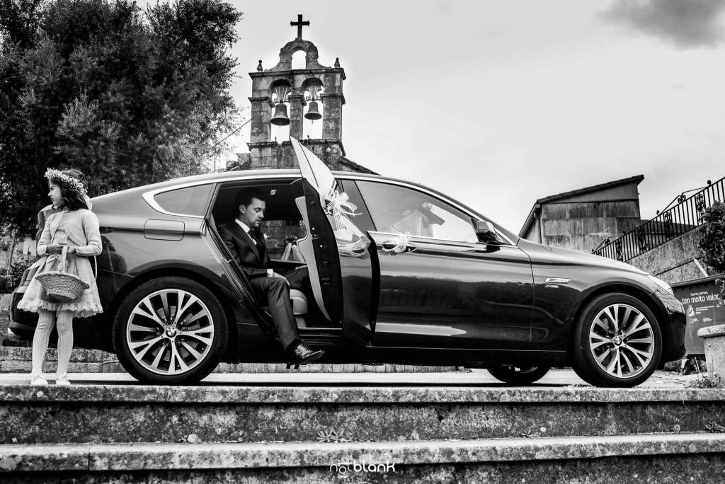 Boda en Salceda de Caselas. El novio se baja de un BMW al llegar a la iglesia. Reportaje realizado por Notblank fotógrafos de boda en Galicia.