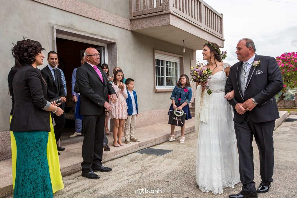Boda en Salceda de Caselas. La novia del brazo del padre saluda a los invitados en casa de los padres antes de emprender camino hacia la iglesia. Reportaje realizado por Notblank fotógrafos de boda en Galicia.