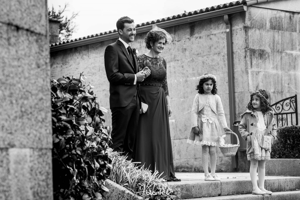 Boda en Salceda de Caselas. El novio ya su madre reciben a los invitados a la puerta de la iglesia. Reportaje realizado por Notblank fotógrafos de boda en Galicia.