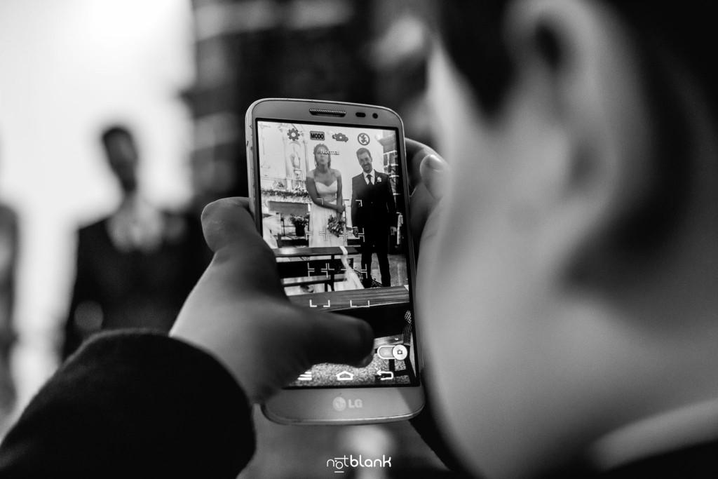 Boda en Salceda de Caselas. Un niño invitado a la boda quita una foto con un móvil a los novios en la iglesia. Reportaje realizado por Notblank fotógrafos de boda en Galicia.