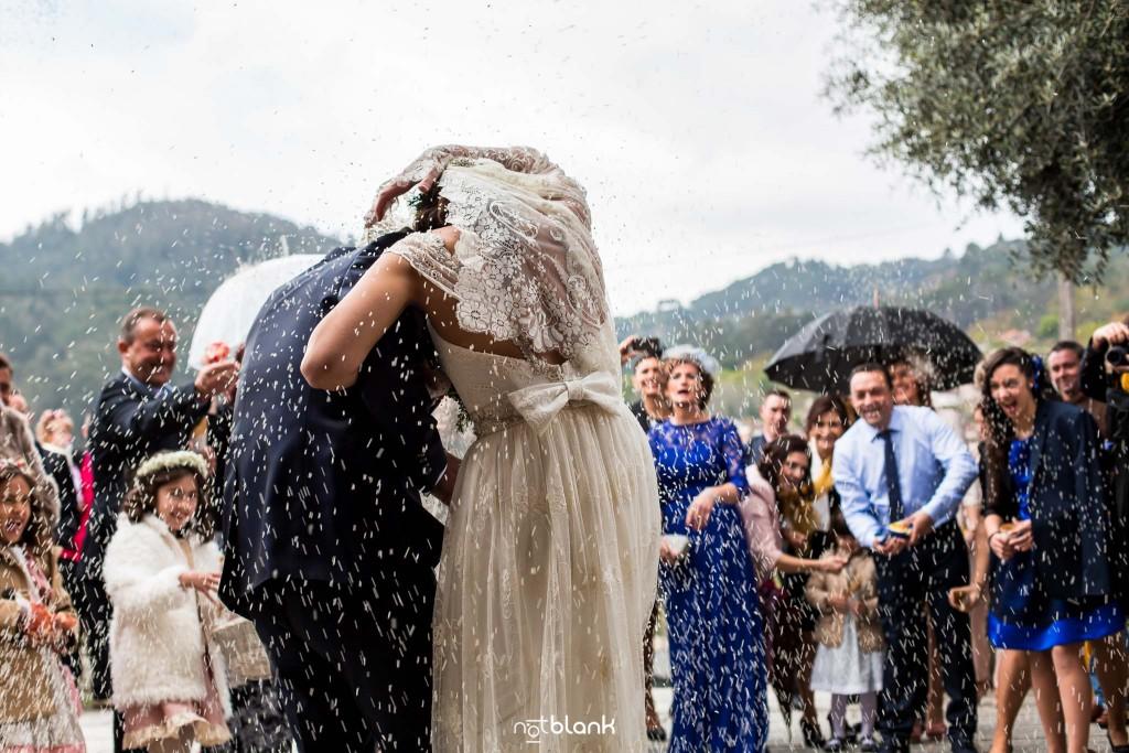 Boda en Salceda de Caselas. Los invitados tiran una gran lluvia de arroz a la salida de los novios de la iglesia. Reportaje realizado por Notblank fotógrafos de boda en Galicia.