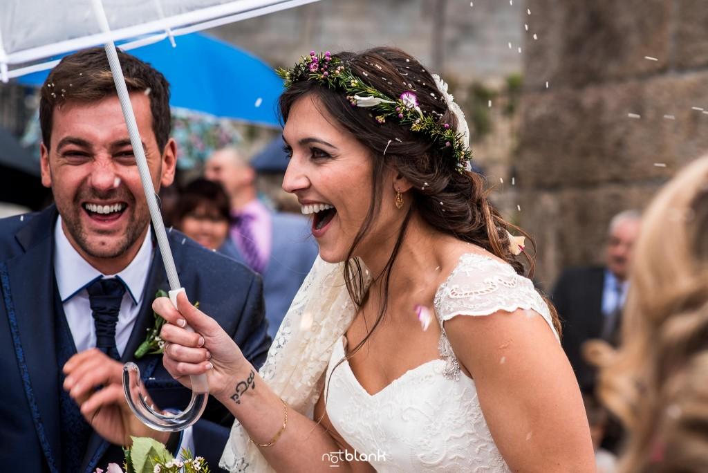 Boda en Salceda de Caselas. Expresión de los novios tras la gran lluvia de arroz a la salida de la iglesia. La novia sostiene un paraguas para refugiarse de la lluvia de arroz. Reportaje realizado por Notblank fotógrafos de boda en Galicia.