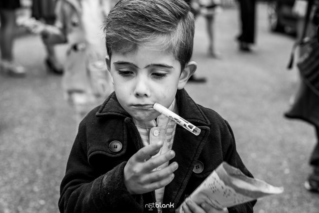 Boda en Salceda de Caselas. Un niño juega con un matasuegras a la salida de la ceremonia. Reportaje realizado por Notblank fotógrafos de boda en Galicia.