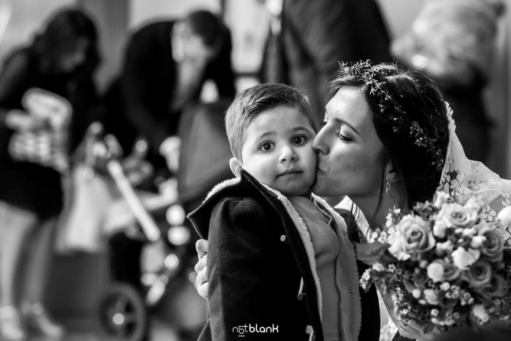 Boda en Salceda de Caselas. La novia le da un beso a su sobrino. Reportaje realizado por Notblank fotógrafos de boda en Galicia.