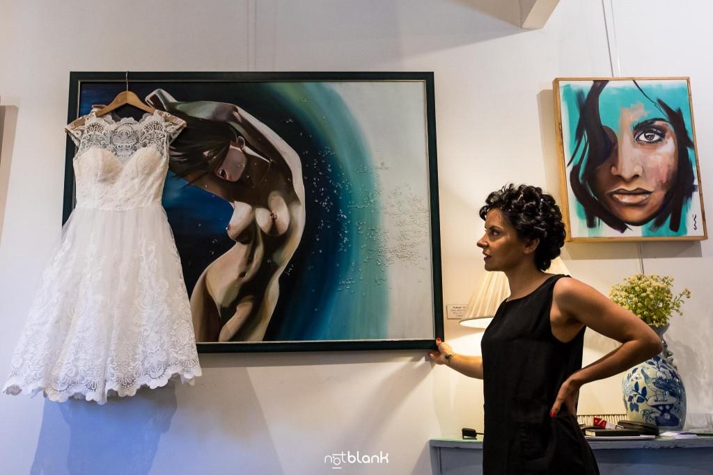 Boda en Quinta San Amaro en Meaño. La novia mira atentamente para su precioso vestido colgado de un oleo en la pared. Reportaje realizado por Notblank fotógrafos de boda en Cangas.