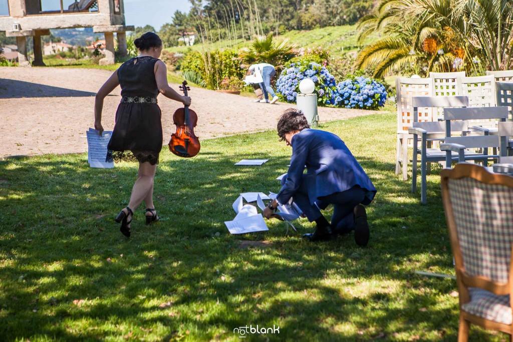 Boda en Quinta San Amaro en Meaño. El sobrino de la novia ayuda a la violinista a recoger las partituras que han salido volando debido al viento. Reportaje realizado por Notblank fotógrafos de boda en Cangas.