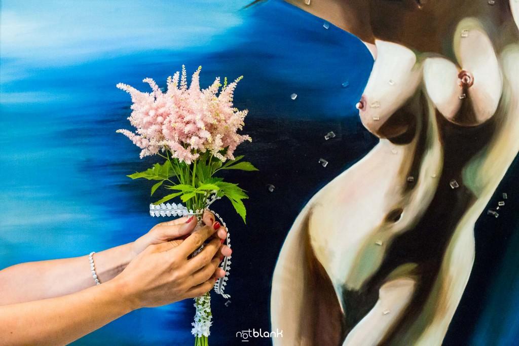 Boda en Quinta San Amaro en Meaño. Detalle del ramo de la novia junto al óleo de una chica desnuda. Reportaje realizado por Notblank fotógrafos de boda en Cangas.