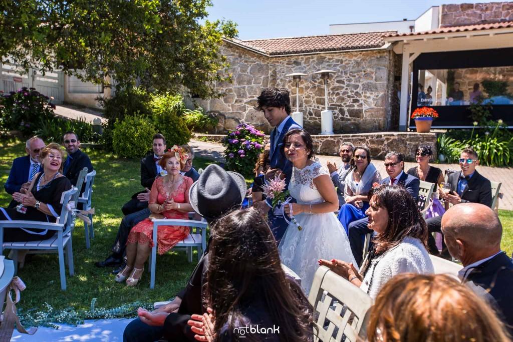 Boda en Quinta San Amaro en Meaño. Los invitados reciben a la novia que viene de brazo de su sobrino. Reportaje realizado por Notblank fotógrafos de boda en Cangas.
