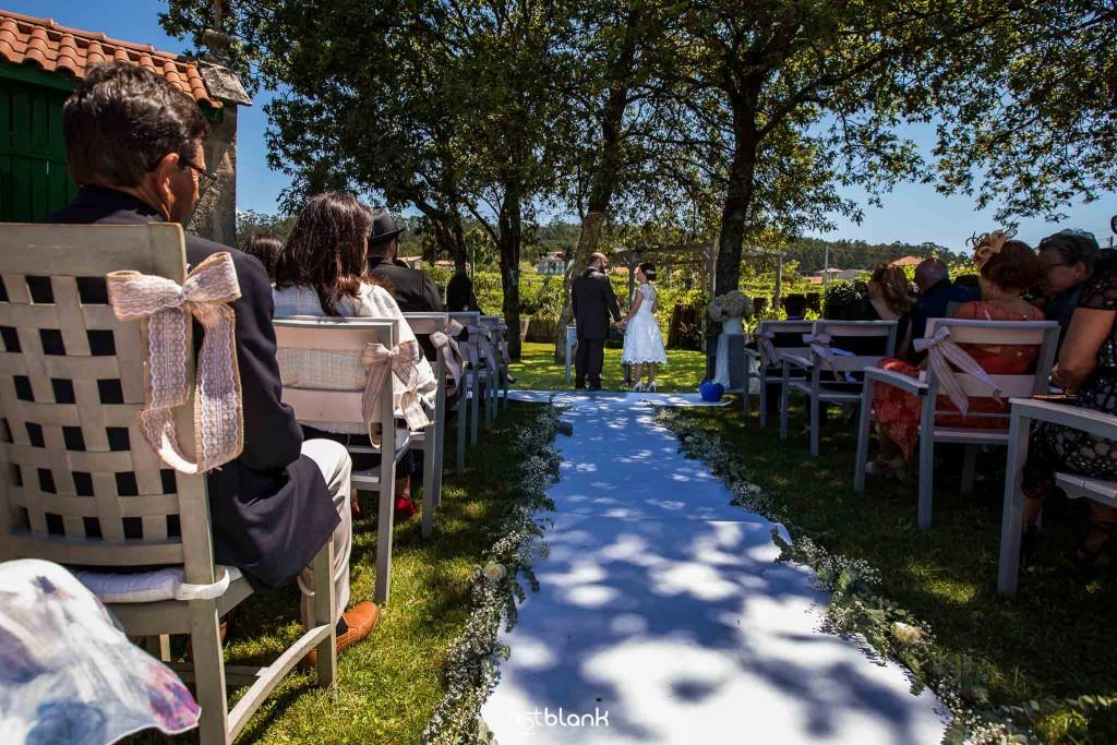 Boda en Quinta San Amaro en Meaño. Los novios están en el altar y los invitados los observan. Reportaje realizado por Notblank fotógrafos de boda en Cangas.