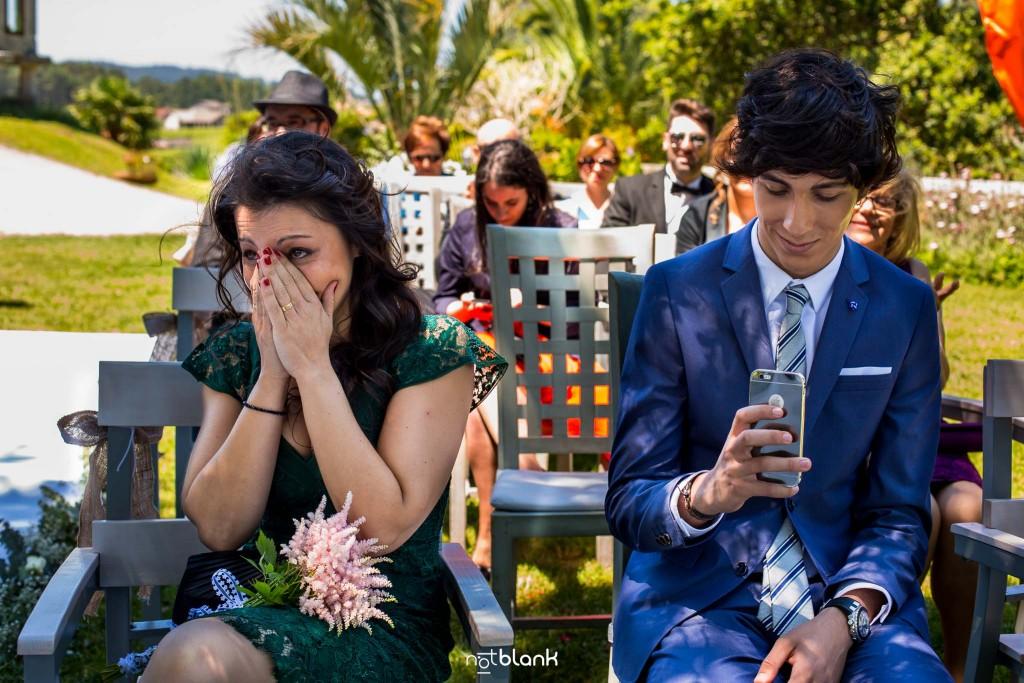 Boda en Quinta San Amaro en Meaño. La hermana de la novia se emociona y llora durante la ceremonia civil. El sobrino de la novia graba con su teléfono móvil la ceremonia. Reportaje realizado por Notblank fotógrafos de boda en Cangas.