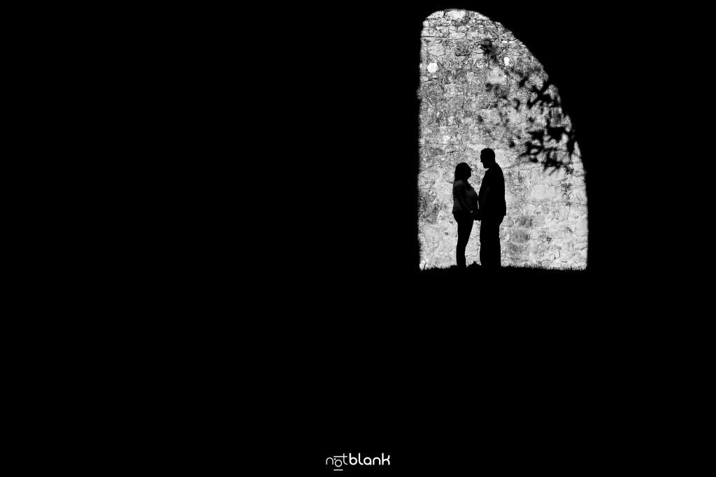 Preboda internacional en Valença do Minho. Silueta de los novios enmarcados en un pasadizo de la fortaleza. Reportaje de sesión preboda realizado por Notblank fotógrafos de boda en Galicia.