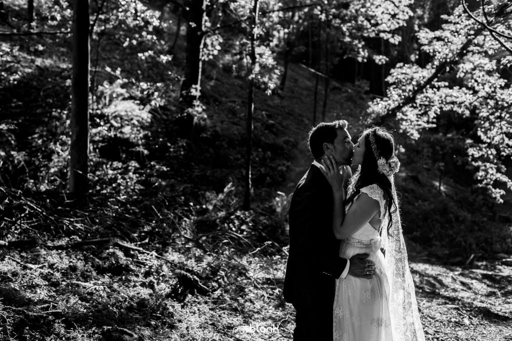 Sesión Postboda en Portugal. La pareja se besa apasionadamente en el bosque. Reportaje realizado por Notblank fotógrafos de boda en Galicia.