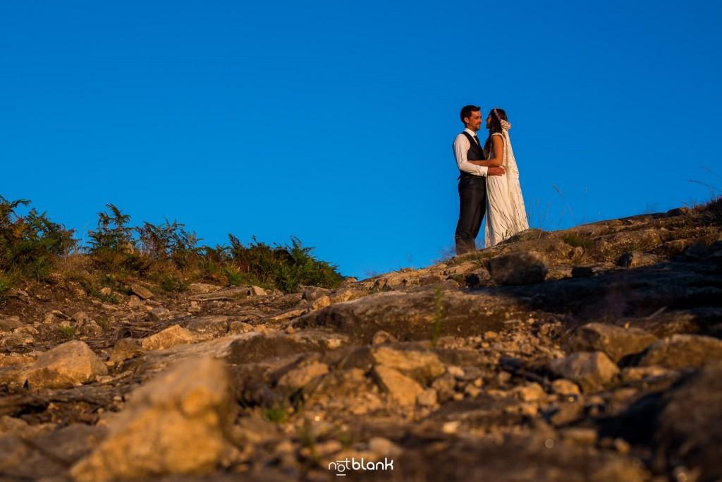 Sesión Postboda en Portugal. La pareja se abraza en la montaña con el sol del atardecer. Reportaje realizado por Notblank fotógrafos de boda en Galicia.