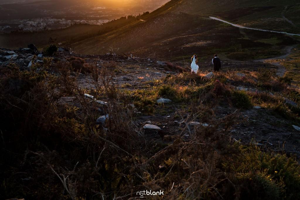 Sesión Postboda en Portugal. La pareja camina en la montaña hacia la puesta de sol del atardecer. Reportaje realizado por Notblank fotógrafos de boda en Galicia.