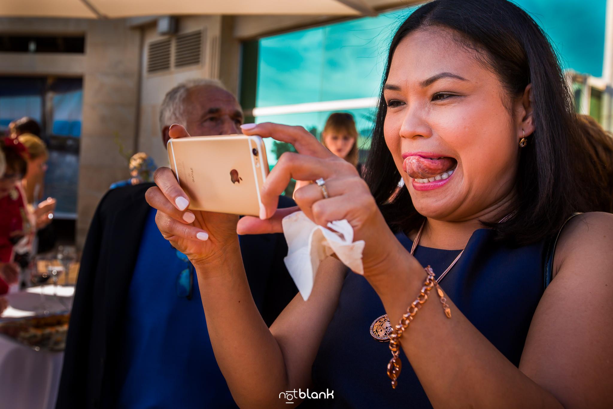 Boda De Destino de Maite David. Una Amiga Saca Foto Con Iphone y la Lengua de Fuera. Reportaje realizado por Notblank Fotografos de boda