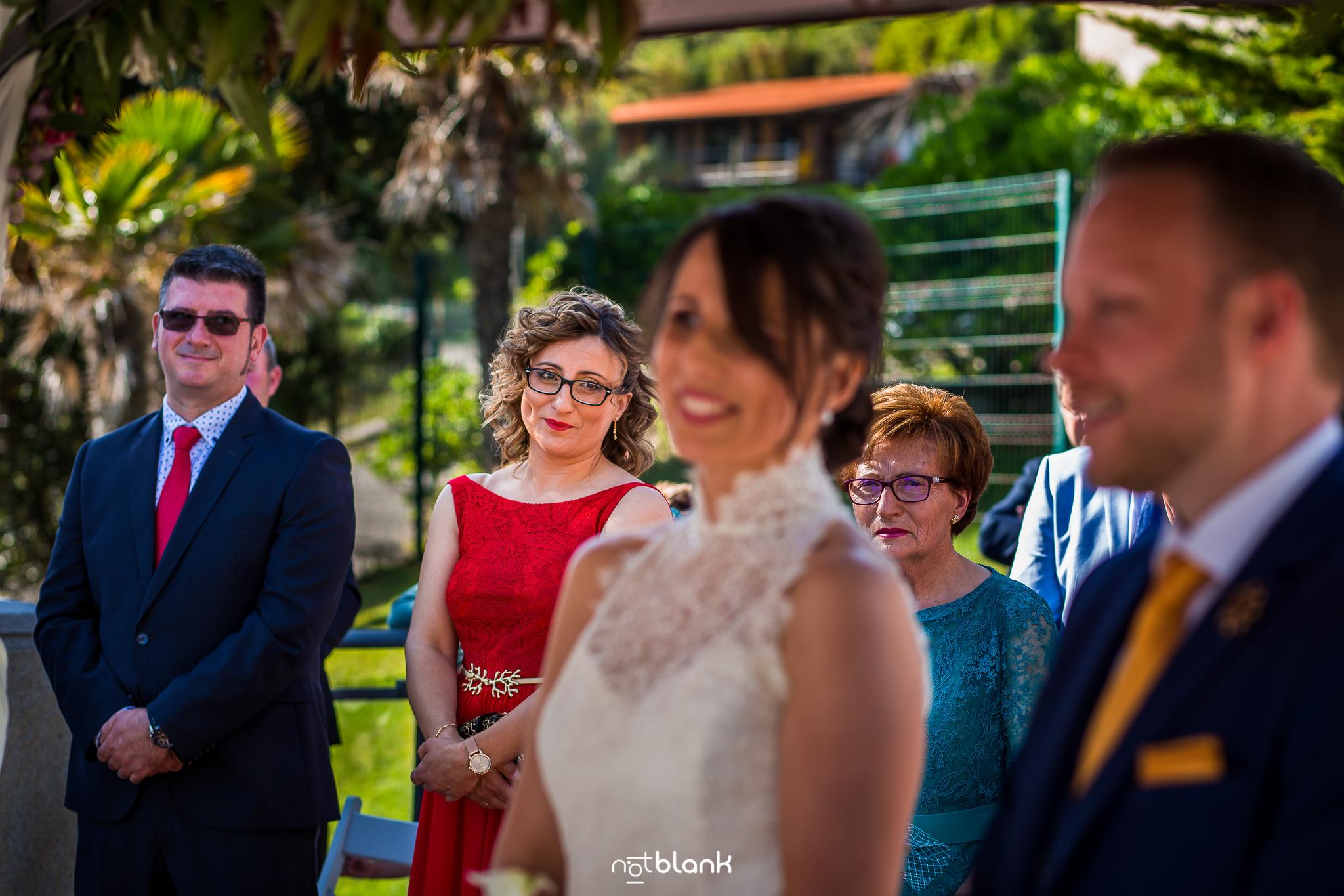 Boda-Maite-David-Hermana-De-La-Novia-Observa-A-Novios-En-El-Altar.Reportaje realizado por Notblank Fotografos de boda