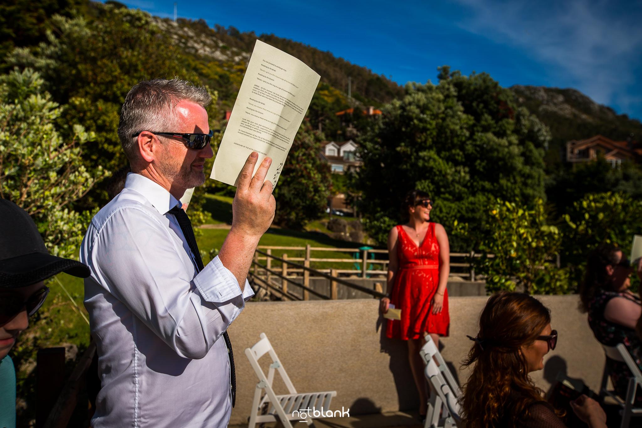 Boda-Maite-David-Invitado-Se-Proteje-Del-Sol-En-Ceremonia-Civil-Talaso-Atlantico. Reportaje realizado por Notblank fotógrafos de boda