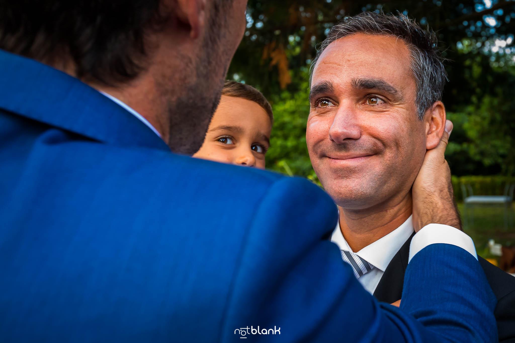 Boda En El Jardin De Casa Jana y Fran - Un amigo del novio mira con ojos llorosos y cara de alegria al novio mientras este le abraza - Notblank Fotografos de boda