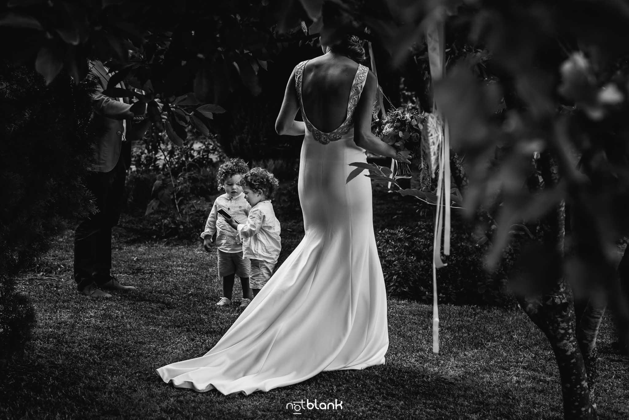 Boda En El Jardin De Casa Jana y Fran - La novia mira a dos hermanos gemelos que juegan con un telefono movil - Notblank Fotografos de boda