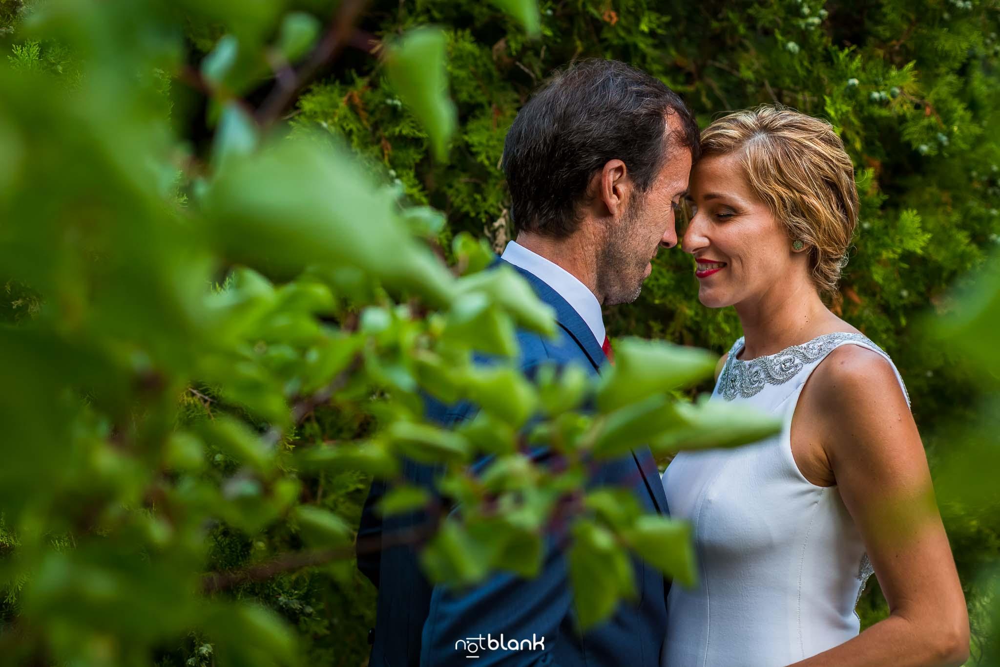 Boda En El Jardin De Casa Jana y Fran - Los novios de abrazan detras de unos arboles - Notblank Fotografos de boda