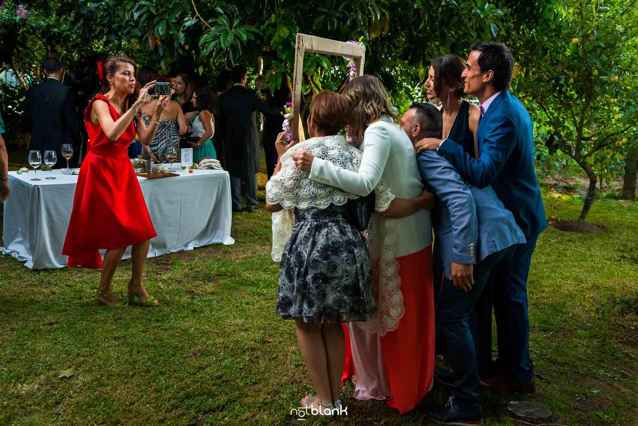 Boda En El Jardin De Casa Jana y Fran - La hermana de la novia con un vestido rojo hace una foto con un telefono movil a varios invitados - Notblank Fotografos de boda