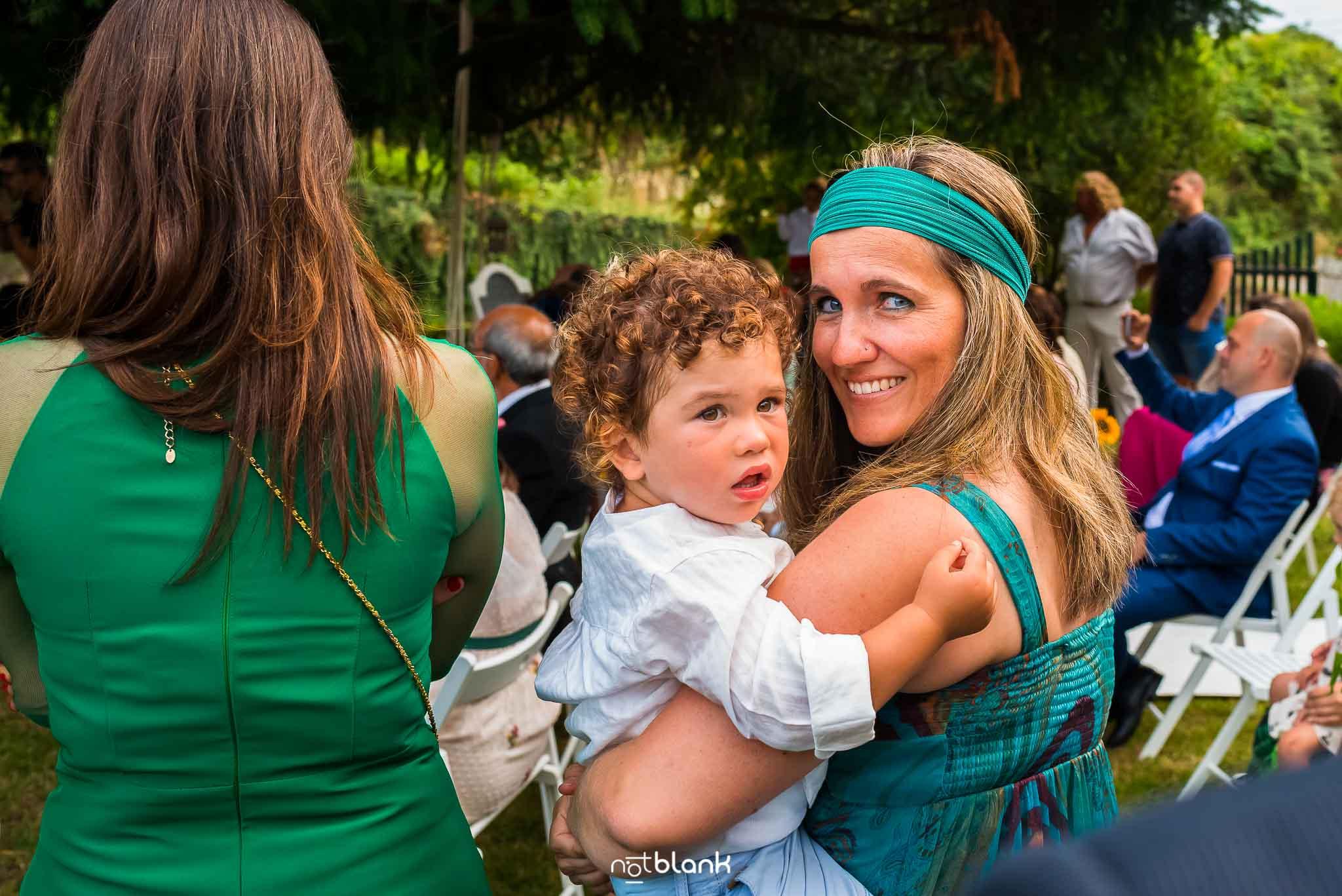 Boda En El Jardin De Casa Jana y Fran - Una invitada sostiene a su hijo en el colo durante la ceremonia civil - Notblank Fotografos de boda