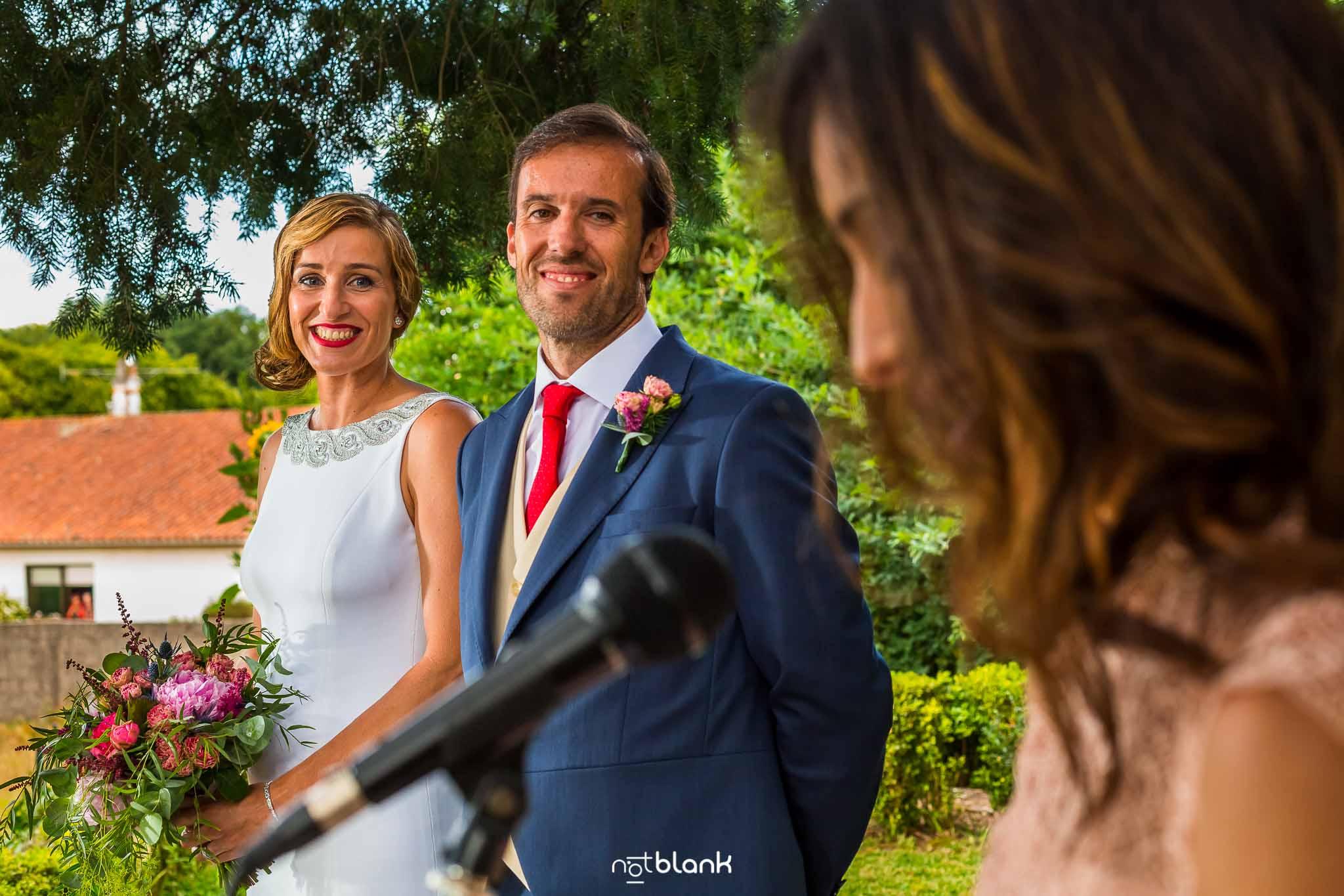 Boda En El Jardin De Casa Jana y Fran - Los novios miran sonrientes a la hermana del novio mientras esta pronuncia unas palabras durante la ceremonia - Notblank Fotografos de boda
