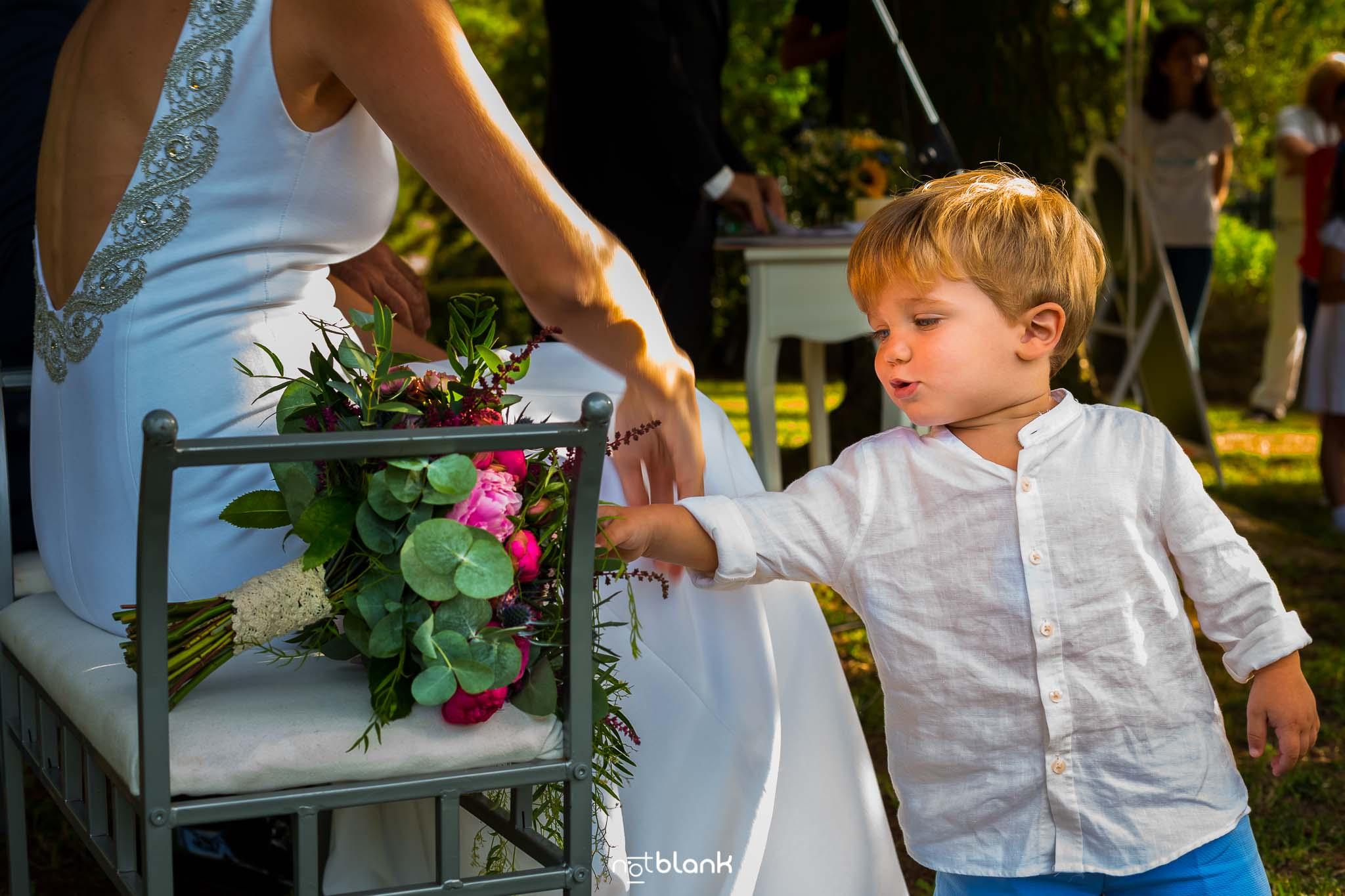 Boda En El Jardin De Casa Jana y Fran - El hijo pequeño de los novios se acerca al ramo de flores de la novia para jugar con el - Notblank Fotografos de boda