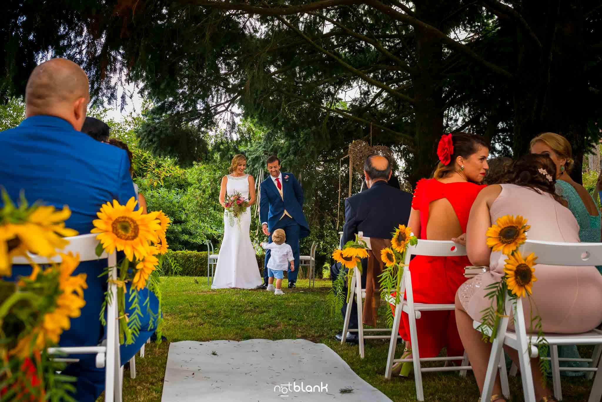 Boda En El Jardin De Casa Jana y Fran - Los novios miran sonriendo a su hijo pequeño que se acba de acercar a ellos durante la ceremonia civil - Notblank Fotografos de boda
