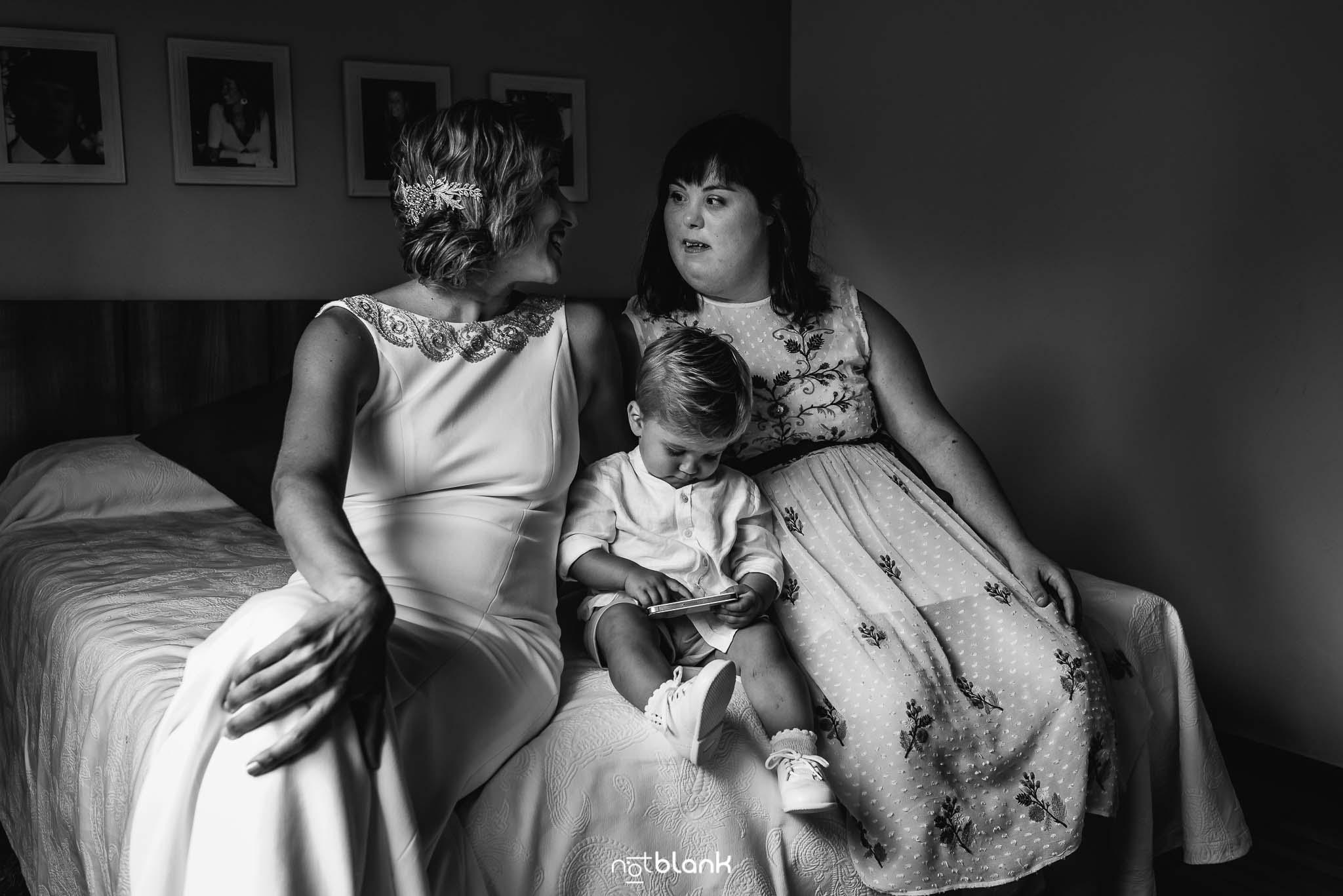 Boda En El Jardin De Casa Jana y Fran - La novia, su hijo pequeño y la hermana de la novia charlan sentadas encima de la cama - Notblank Fotografos de boda
