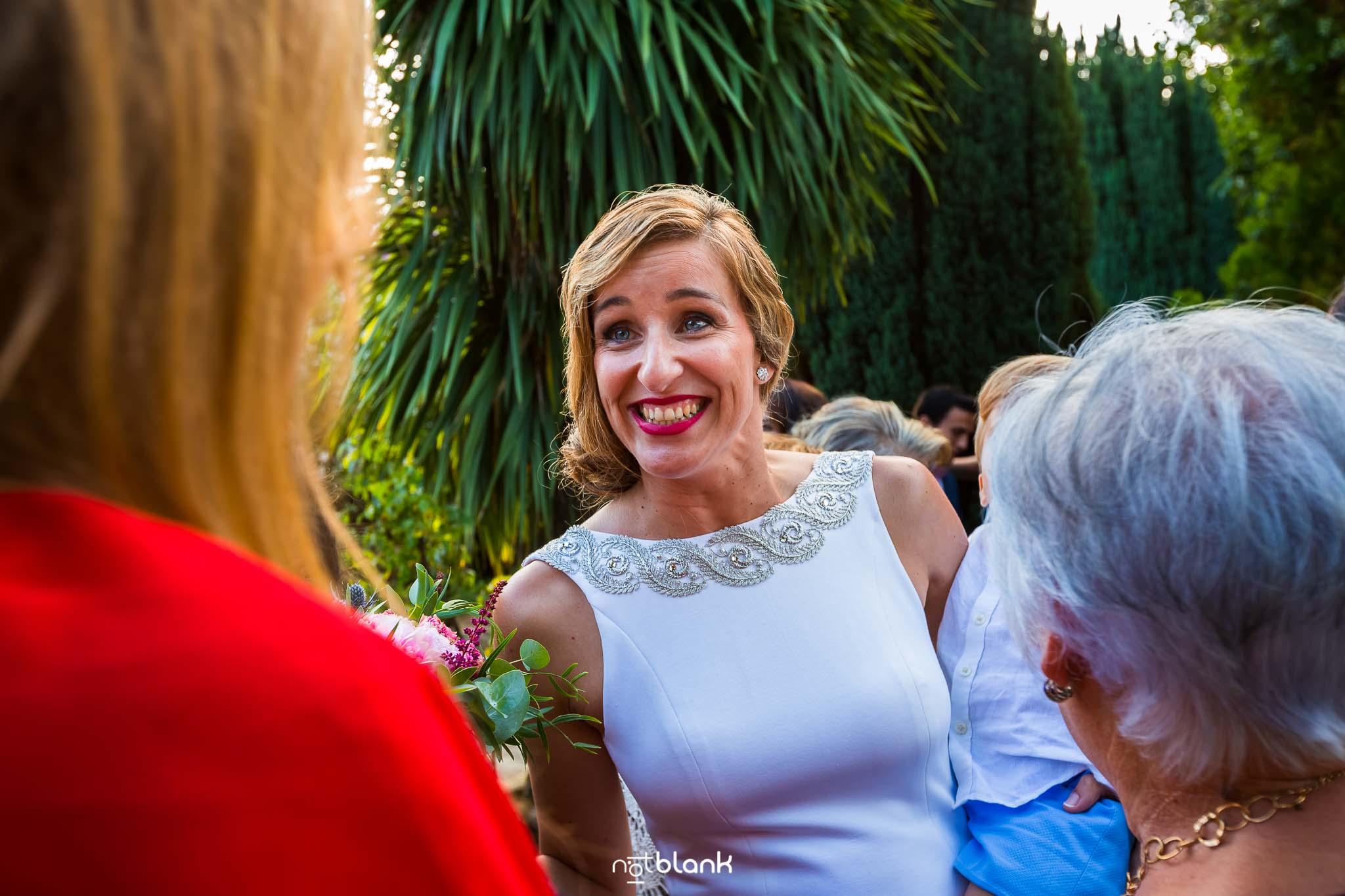 Boda En El Jardin De Casa Jana y Fran - La novia sonrie mientras la felicitan por su boda civil - Notblank Fotografos de boda