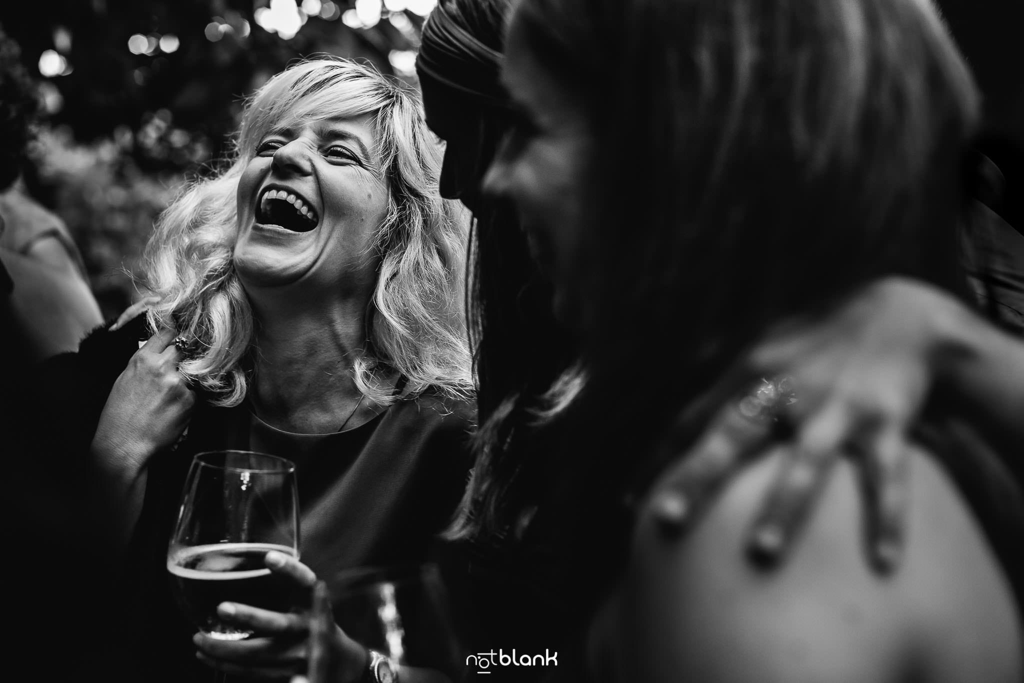 Boda En El Jardin De Casa Jana y Fran - Una invitada rie a carcajada limpia durante el cocktail de la boda civil - Notblank Fotografos de boda