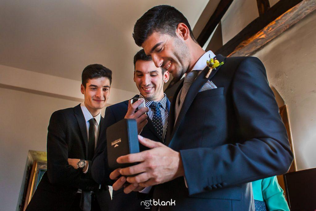 El novio junto a sus hermanos mira el reloj que le ha regalado su novia