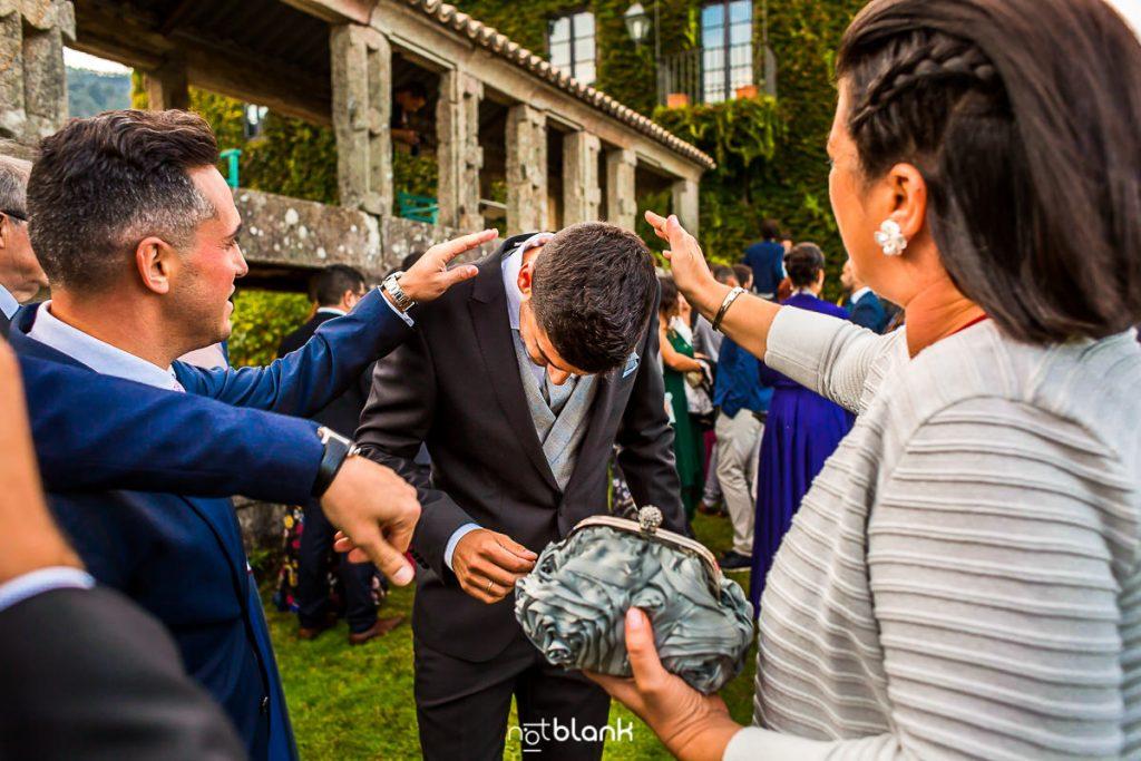 Los amigos del novio le ayudan a sacarse los pétalos del traje