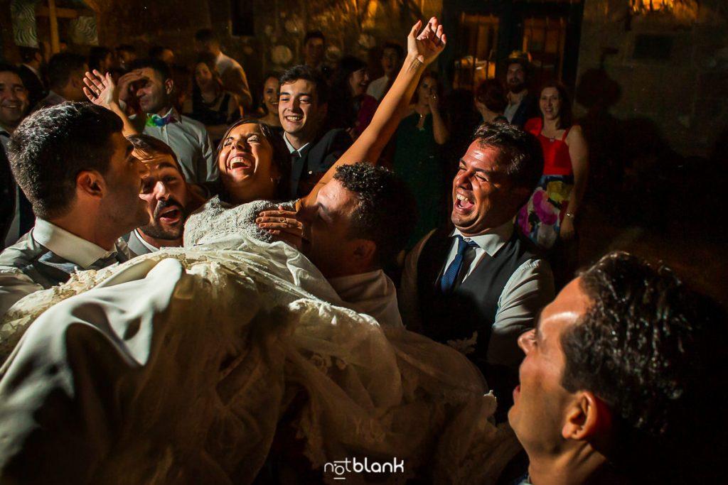 Los amigos de los novios aúpan a la novia durante la fiesta